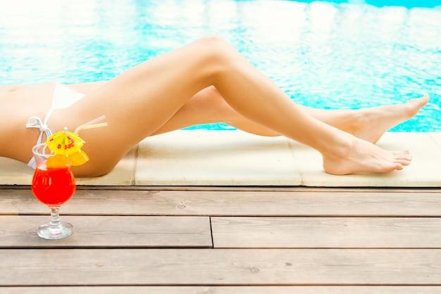 Расслабляющий бассейн. вид сбоку красивых женских ножек у бассейна с коктейлем на переднем плане