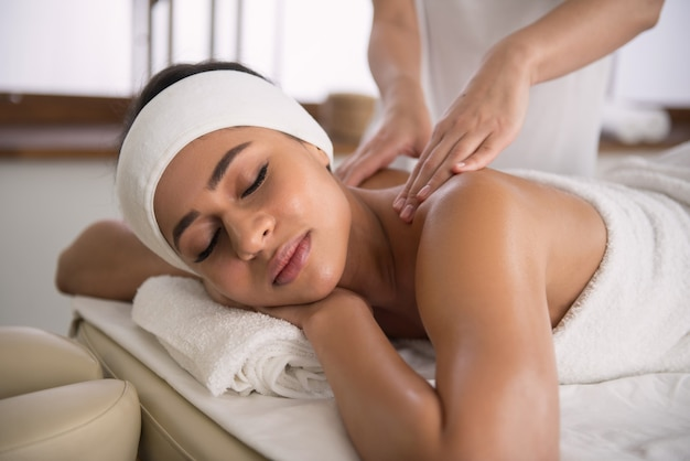 Расслабляющая процедура. милая приятная расслабленная женщина закрыла глаза во время профессионального массажа в спа-салоне