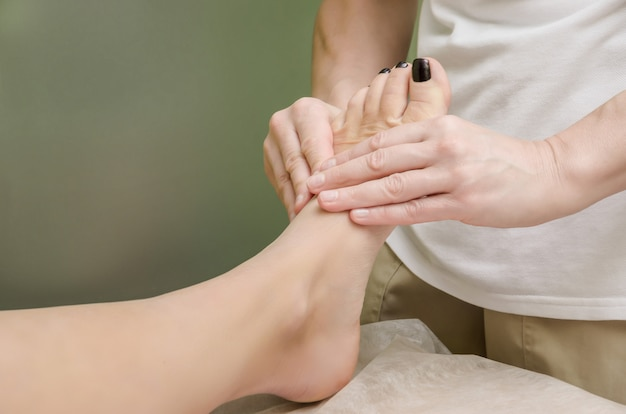 Relaxing professional massage on the female foot in the salon.