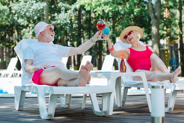 Relaxing retired man and woman drinking summer cocktails while sunbathing near the pool