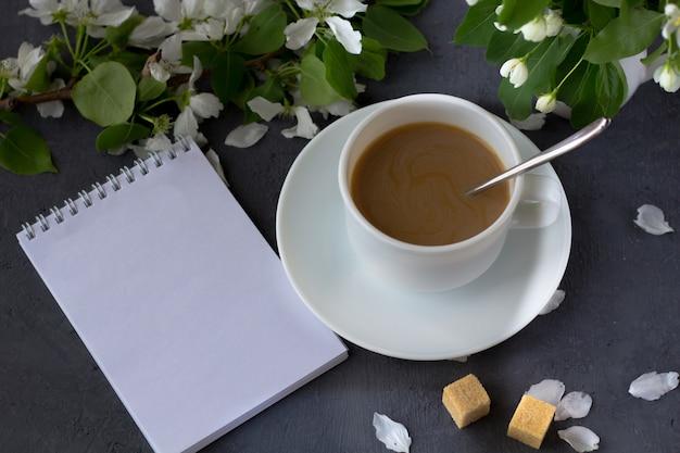 Расслабляющий время и счастье с чашкой кофе с среди свежего весеннего цветка. утренний кофе в солнечный день. блокнот с пространством для текста.