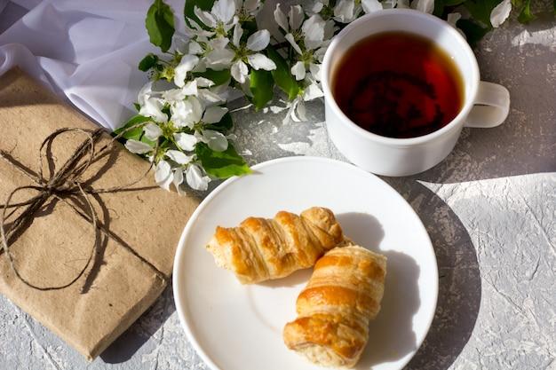新鮮な春の花の中でお茶を飲みながらリラックスした時間と幸せ。暖かい晴れた日のケーキと朝のお茶。