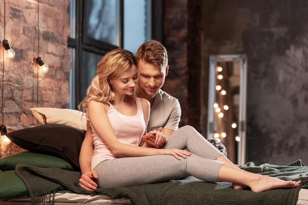 ゆったりとした時間。寝室でリラックスした時間を過ごすパジャマを着たかわいい愛情のある素晴らしいカップル