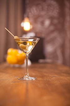 Relaxing time in restaurant with a glass of martini and green olives. fresh drink. tasty drink.