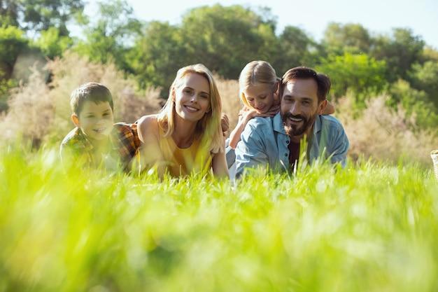 함께 휴식. 그녀의 가족과 함께 잔디에 누워 웃 고 아름 다운 젊은 어머니