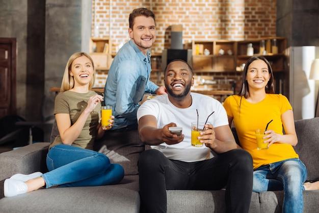 Отдыхаем вместе. четыре радостных симпатичных подруги сидят на диване, наслаждаются соком и смеются