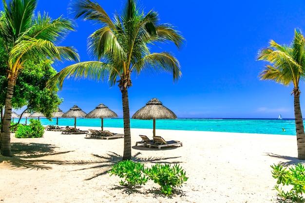 Расслабляющий тропический отдых, шезлонги и зонтики на белом песчаном пляже острова маврикий