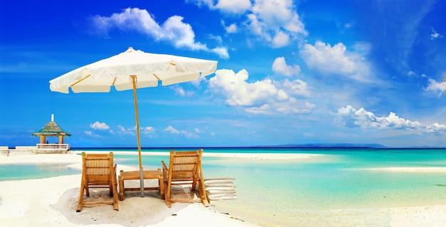 편안한 열대 휴가, 하얀 모래 해변에 비치 의자 2 개가있는 우산