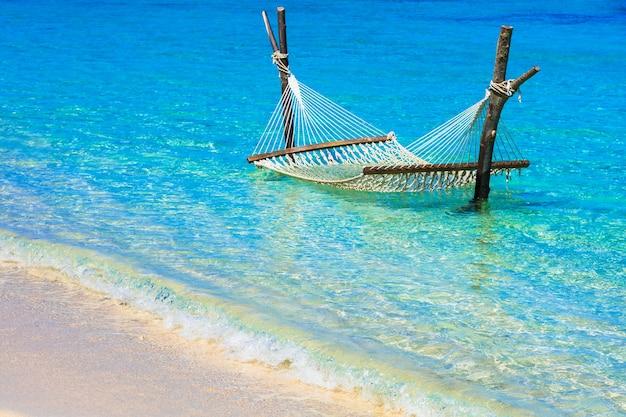 ターコイズブルーの水にハンモックでリラックスした熱帯の休日