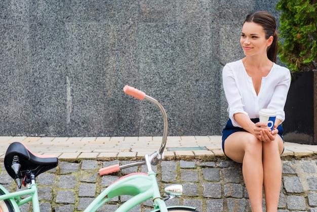 淹れたてのコーヒーでリラックス。彼女のビンテージ自転車の近くの道端に座っている間コーヒーカップを保持している魅力的な若い女性