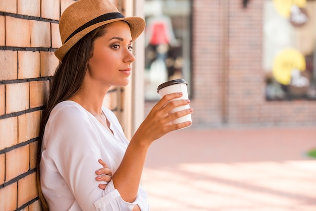신선한 커피 한잔과 함께 휴식. 펑키한 모자를 쓴 사려 깊은 젊은 여성이 뜨거운 음료와 함께 컵을 들고 야외에서 벽에 기대어 시선을 돌리는 모습