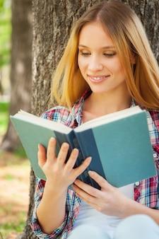 좋은 책과 함께 힐링하세요. 공원에서 나무에 기대어 책을 읽고 웃고 있는 아름다운 젊은 여성