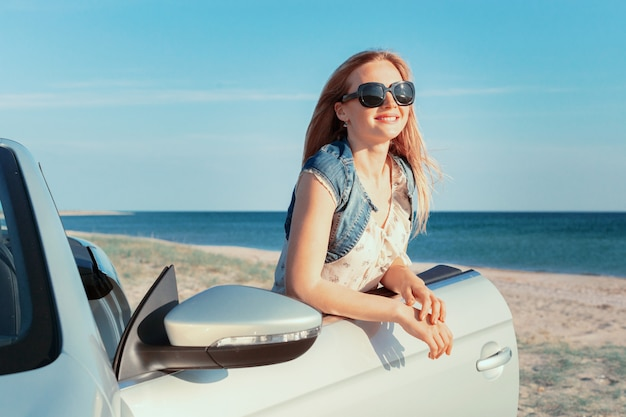Relaxing woman on the beach in the car