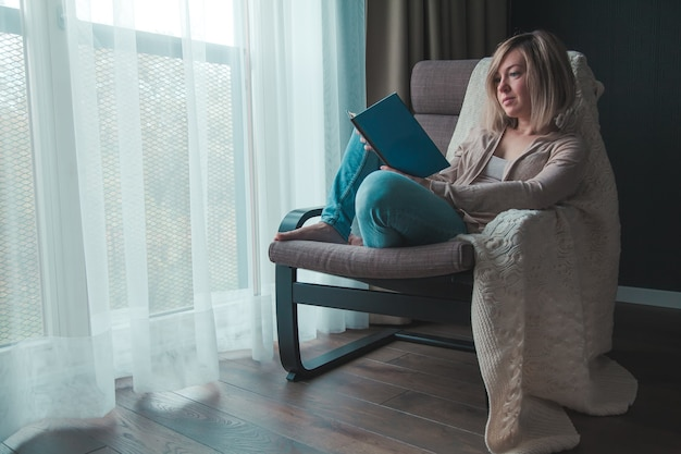 Расслабляющая женщина изолирует дома, она читает книгу, сидя в кресле у окна