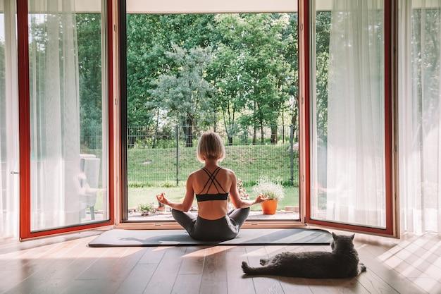 Расслабляющая женщина, сидящая в позе лотоса перед открытым окном, занимаясь йогой дома. ее кот смотрит на нее, лежа рядом с ней.