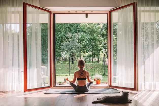 Расслабляющая женщина, сидящая в позе лотоса перед открытым окном, занимаясь йогой дома. ее кот наблюдает за ней.