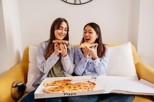 Donne rilassanti che mangiano pizza
