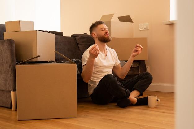 Расслабляющий молодой человек сидит на полу и медитирует. европейский парень с закрытыми глазами возле дивана. картонные коробки с вещами. концепция переезда в новую квартиру. интерьер однокомнатной квартиры
