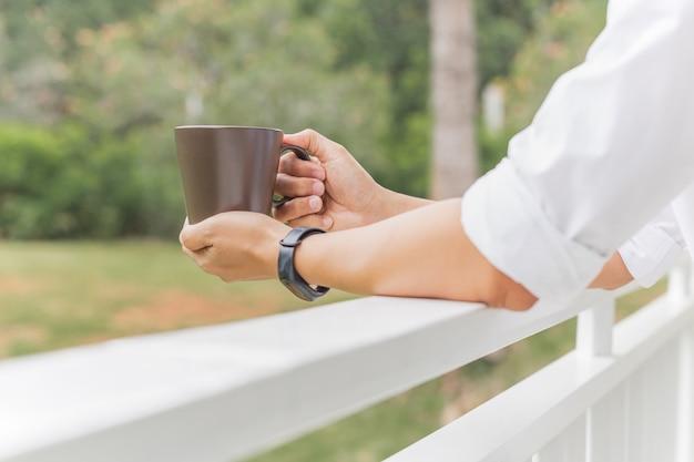 バルコニーに立っている間コーヒーマグを持っている男relaxjng手。
