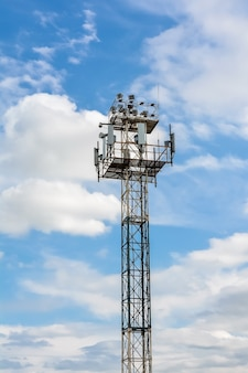 Relay telephone and radio transmission tower against a blue sky with clouds