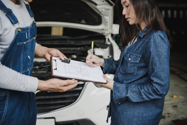 Reliable auto mechanic showing clipboard to a female customer