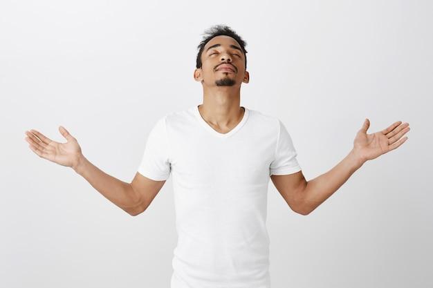 安心して笑顔のアフリカ系アメリカ人の男性が目を閉じて感謝の気持ちで手を上げる