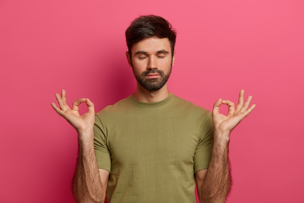 Relieved bearded young man relaxes during meditation, keeps eyes closed, spreads palms sideways in nirvana, wears casual t shirt, practices yoga, inhales fresh air, isolated on pink  wall