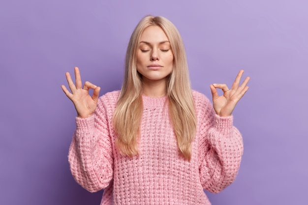Relieved calm blonde woman searches peace inside makes mudra gesture reaches nirvana and breathes deeply with closed eyes
