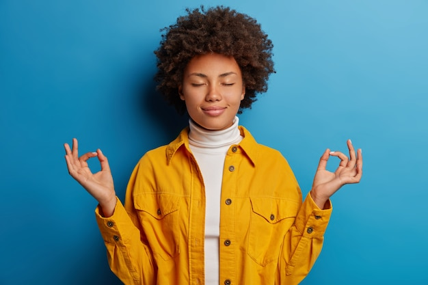 Relieved calm dark skinned woman closes eyes, makes mudra gesture, dressed in yellow shirt, feels relaxed, poses against blue background
