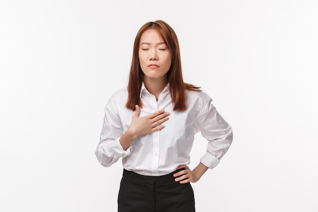 Relieved and chill-out asian woman trying breath and be calm, touch chest breathing peaceful, close eyes, ease stress, standing white wall getting ready for presentation