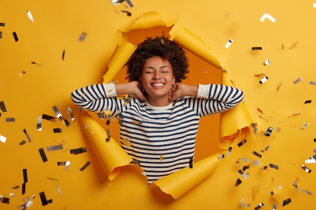 Relieved dark skinned woman has eyes closed, smiles broadly, keeps hands behind head, poses in paper hole of bright wall