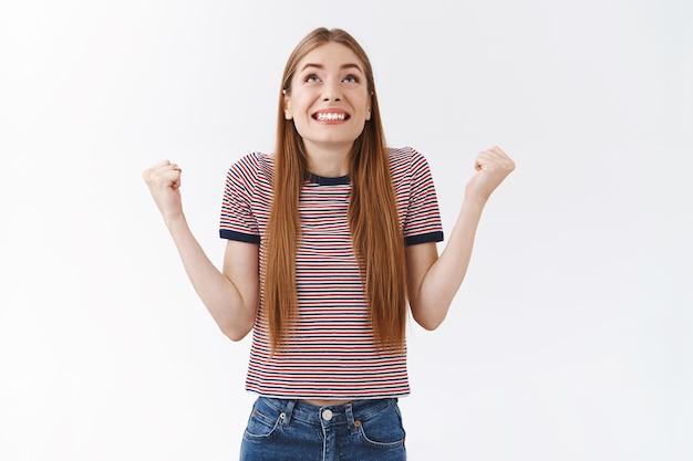 줄무늬 티셔츠를 입은 편안하고 행복한 미모의 여성은 신에게 감사를 표하고 즐겁게 주먹을 쥔 채 하늘을 바라보며 기쁘게 웃고, 멋진 소식에서 승리하고, 기쁘게 서서 승리를 축하합니다.