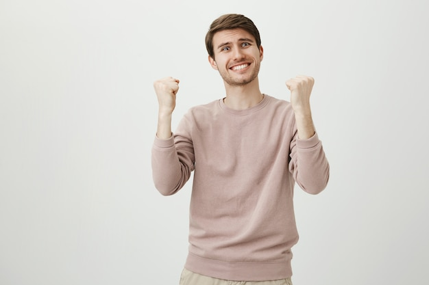 Relieved happy man rejoicing over good news, fist pump triumphing