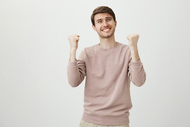 Облегченный счастливый человек радуется хорошим новостям, торжествует кулак