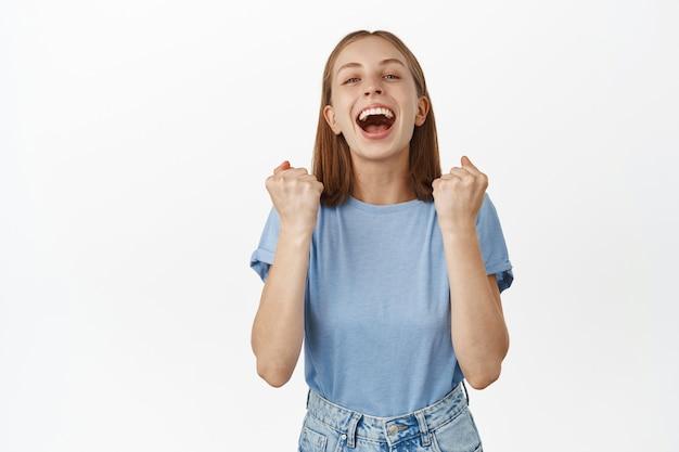 La giovane donna sollevata e felice urla dal successo e dal trionfo, fa pompare il pugno, gridando gioiosa, esulta come vincente, raggiunge l'obiettivo, in piedi contro il muro bianco