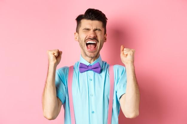 행복과 기쁨에서 외치는 안심 된 남자는 눈을 감고 주먹을 움켜 쥐고 승리를 축하하고 목표를 달성하고 승리하며 분홍색 배경 위에 서 있습니다.