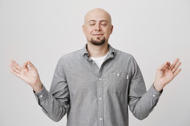С облегчением улыбающийся лысый парень медитирует, чувствуя покой