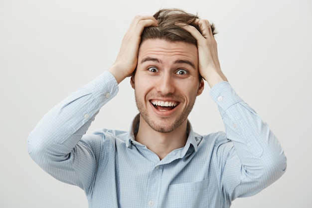 Relieved surprised man smiling, tossing hair astonished