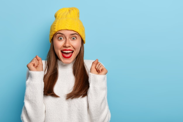 La donna trionfante sollevata inclina le mani in allegria, stringe i pugni, indossa un rossetto rosso, ha i capelli lisci scuri, indossa abiti alla moda, isolato su sfondo blu