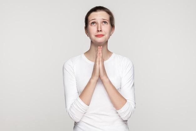 종교 개념입니다. 기도하는 소녀. 스튜디오 촬영, 회색 배경에 고립