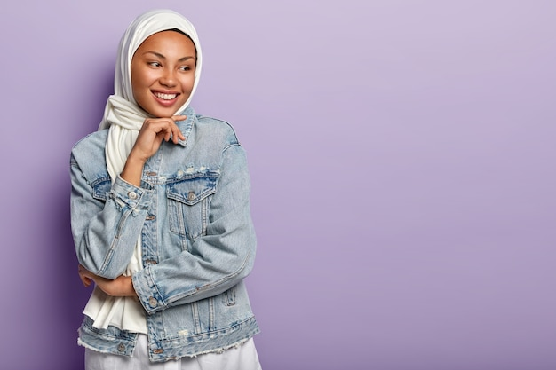 Religious arabic woman has cheerful expression, covers head with white hijab, wears denim jacket, holds chin, looks away, stands against purple wall. people, ethnicity and faith concept