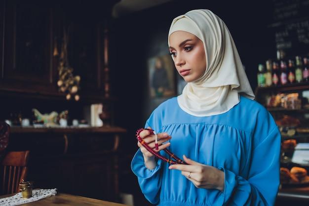 ロザリオビーズを持って手で祈る宗教的なアジアの仏教徒の女性。瞑想する女性の仏教徒の弟子
