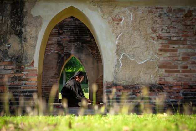 종교적인 아시아 무슬림 남자는 집에서 묵주를 들고 신에게 기도합니다. 창문을 통해 빛나는 일몰. 평화롭고 놀라운 따뜻한 기후. 선택적 집중.
