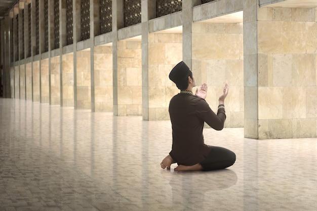 Religious asian muslim man raising hand and praying