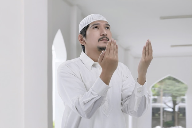 Religious asian muslim man with white cap praying
