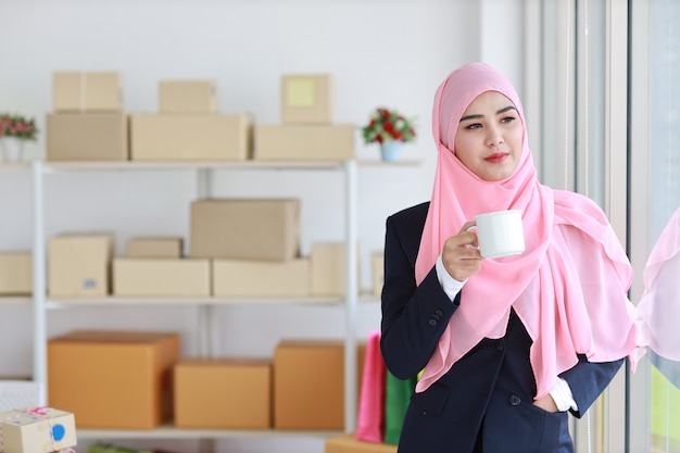 Religious asian muslim woman in blue suit drinking coffee, smiling and pink scarf on head with package box delivery background. startup small business sme freelance girl work at home with happy face