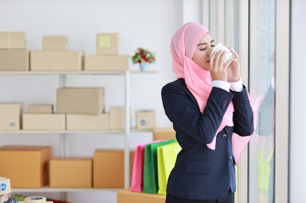 Religious asian muslim woman in blue suit drinking coffee, smiling and pink scarf on head