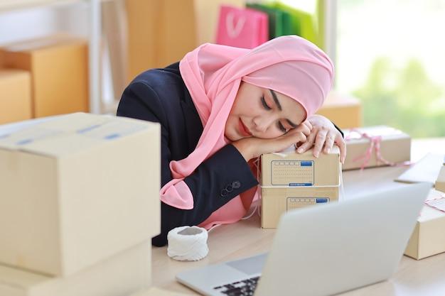 파란색 정장과 분홍색 샤프트에 종교적인 아시아 이슬람 여자는 테이블에 그녀의 머리를 누워 좌절