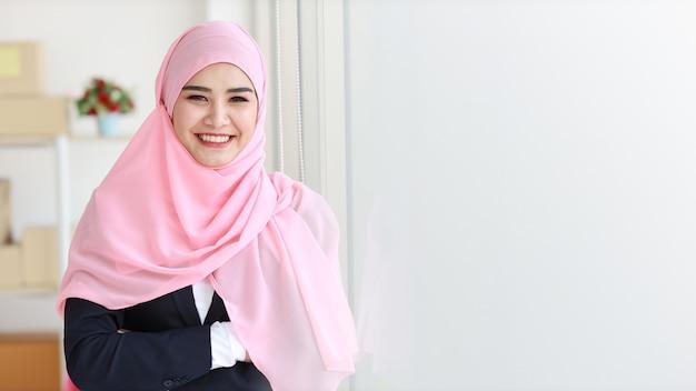 파란색 양복을 입고 머리에 분홍색 샤프트를 착용하고 자신감 있게 카메라를 바라보는 종교적인 아시아 이슬람 여성. 비즈니스 우먼은 패키지 sme 상자 배달 배경으로 서 있습니다. 집에서 일하기 개념