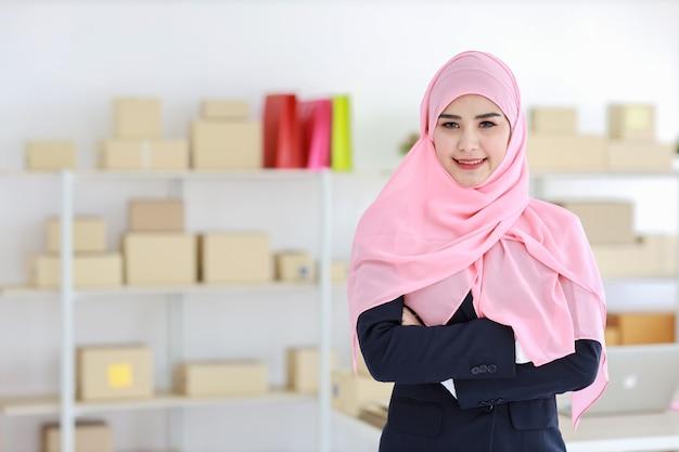 Религиозная азиатская мусульманка в синем костюме и розовом валу на голове стоит и уверенно смотрит в камеру
